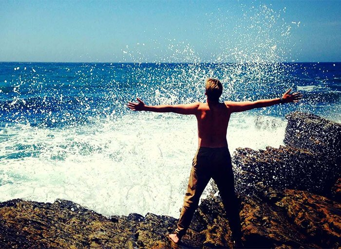 Man standing with arms wide open on edge of rocks in front of crashing waves